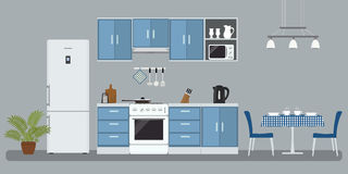 Kitchen in a blue color. There is a furniture, a stove, a refrigerator, a microwave, a kettle and other objects in the picture. There is also a table and Royalty Free Stock Photos