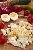 Kitchen board with finely chopped eggs Stock Photos