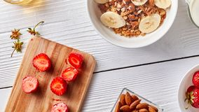 On the kitchen board halves of ripe strawberries, a plate with granola and banana, nuts of almonds on a white kitchen Royalty Free Stock Photography