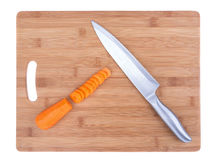 Kitchen board and knife for cutting carrots. Royalty Free Stock Image