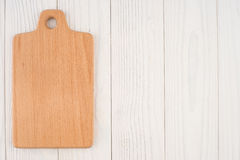 Kitchen board on an old white wooden table. Royalty Free Stock Photo