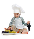Kitchen boy with grape over white background. Child as chef with green and black grape over white background Stock Image
