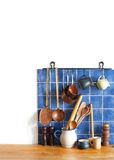 Kitchen brass utensils, chef accessories. Hanging copper kitchenware set. Blue tiles ceramic wall. spoon, pitchers Royalty Free Stock Photo