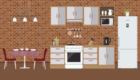 Kitchen on the brick wall background. There is a furniture, a stove, a refrigerator, a microwave, a kettle and other objects in the picture. There is also a Royalty Free Stock Photo