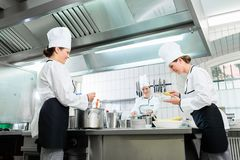 Kitchen staff in canteen preparing dishes. Kitchen brigade in catering kitchen preparing dishes Royalty Free Stock Images