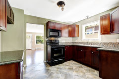 Kitchen with bright burgundy cabinets and black appliances Stock Photos