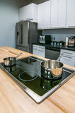 Kitchen butcher table island with stove top and pans Royalty Free Stock Photography