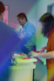 Kitchen Buzz. Blurry movements as busybodies prepare party food in the kitchen. Colored spotlights suggest party about to start Stock Image