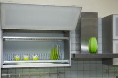 Kitchen cabinet. With green cups and dishes stock images