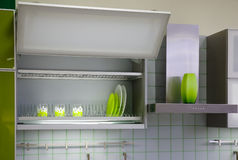 Kitchen cabinet. With green cups and dishes stock photography