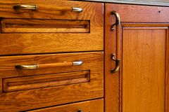 Kitchen cabinet. Beautiful and wooden kitchen cabinet with handles stock photo