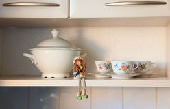 Kitchen cabinet board with a doll and cups. A doll and cups and a bowl on a kitchen shelf royalty free stock images