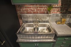 Kitchen cabinet with double steel sink in english style, green table, silver luxury faucet kitchen royalty free stock images