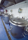 Kitchen cauldrons. Industrial kitchen interior ready for preparing meal. Huge metal cauldrons lined up at the wall Royalty Free Stock Photos