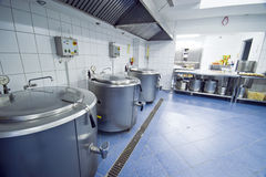 Kitchen cauldrons. Industrial kitchen interior ready for preparing meal. Huge metal cauldrons lined up at the wall Stock Photo
