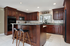 Kitchen with cherry wood cabinetry Royalty Free Stock Images