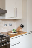 Kitchen with chopping board knife block, cooker & hood Royalty Free Stock Images