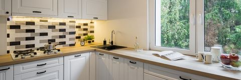 Kitchen with classic white cabinets. Functional kitchen with classic white cabinets, window and wooden worktop, panorama royalty free stock photos