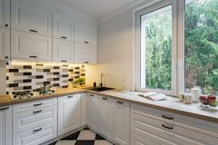Kitchen with classic white cabinets. Functional and bright kitchen with classic white cabinets, wooden worktop and big window royalty free stock photography