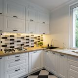 Kitchen with classic cabinets and brick wall. Functional kitchen with classic white cabinets, wooden worktop and black gray white brick wall stock image