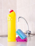 Kitchen cleaning concept. Close up of cleaning product, sponge and cloth on kitchen countertop with faucet in background. Housekeeping concept royalty free stock image