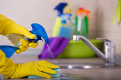Kitchen cleaning concept. Close up of human hand in protective gloves holding sponge and spray bottle and wiping kitchen counter top stock photos