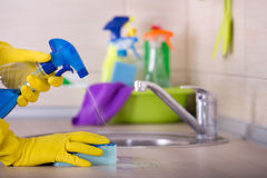 Kitchen cleaning concept. Close up of human hand in protective gloves holding sponge and spray bottle and wiping kitchen counter top royalty free stock images