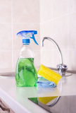 Kitchen cleaning concept. Close up of spray bottle, sponge and cleaning cloth on kitchen countertop with faucet in background. Housekeeping concept stock photo