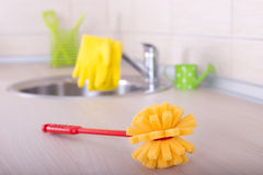 Kitchen cleaning concept. Kitchen cleaning tools. Sponge brush and safety gloves on faucet on the countertop royalty free stock photography