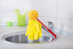 Kitchen cleaning concept. Kitchen cleaning tools. Sponge brush and safety gloves on faucet on the countertop royalty free stock images
