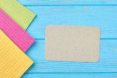 Kitchen cleaning napkin rags. Colorful cellulose sponge cloths and empty paper card on wooden background. Household chores concept stock photos