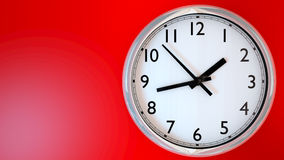Kitchen clock on a red wall. Royalty Free Stock Image