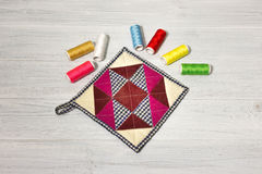 The kitchen cloth potholder for housewives. And colorful threads on wooden table Stock Photo