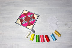 The kitchen cloth potholder for housewives. And colorful threads on wooden table Royalty Free Stock Photography