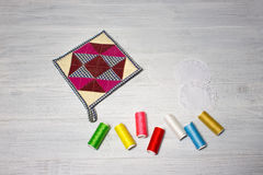 The kitchen cloth potholder for housewives. And colorful threads on wooden table Royalty Free Stock Photos