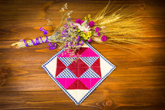 The kitchen cloth potholder for housewives. And dry flowers on wooden table Royalty Free Stock Images