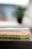 Kitchen Cloths. Three clean kitchen cloths on a table with a window and plant out of focus in the background Royalty Free Stock Image