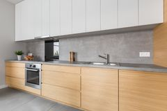 Kitchen with concrete worktop and wooden furniture. Two colored kitchen furniture with concrete worktop and steel appliances Stock Photography
