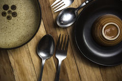 Kitchen containers. Such as plates, bowls, spoons, and cups on the wooden floor Royalty Free Stock Image