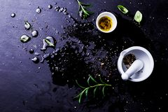 Kitchen and cooking - black messy background with mortar. Kitchen and cooking - dark, moody, messy background. Olive oil, mortar and herbs on black wet counter royalty free stock images