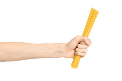 Kitchen and Cooking topic: human hand holding a pile of dry yellow spaghetti isolated on white background in studio Royalty Free Stock Photos