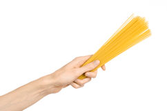 Kitchen and Cooking topic: human hand holding a pile of dry yellow spaghetti isolated on white background in studio Royalty Free Stock Photography