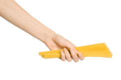 Kitchen and Cooking topic: human hand holding a pile of dry yellow spaghetti isolated on white background in studio Stock Photo
