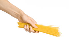 Kitchen and Cooking topic: human hand holding a pile of dry yellow spaghetti isolated on white background in studio Stock Photos