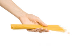 Kitchen and Cooking topic: human hand holding a pile of dry yellow spaghetti isolated on white background in studio Stock Images