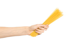 Kitchen and Cooking topic: human hand holding a pile of dry yellow spaghetti isolated on white background in studio Royalty Free Stock Images
