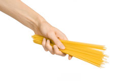 Kitchen and Cooking topic: human hand holding a pile of dry yellow spaghetti isolated on white background in studio Royalty Free Stock Photo