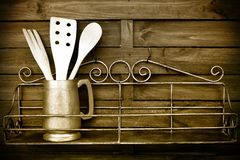 Kitchen cooking utensils on rustic kitchen wall Stock Images