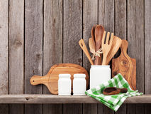 Kitchen cooking utensils on shelf. Against rustic wooden wall Stock Photography