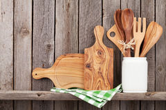 Kitchen cooking utensils on shelf. Against rustic wooden wall Royalty Free Stock Photo